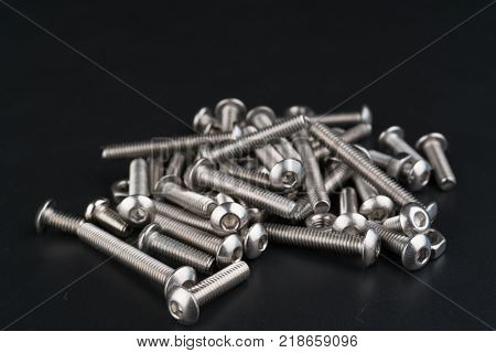 metal fasteners screws and nuts on black background. screw isolated on the black backgrounds. Nuts with bolts closeup