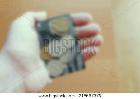 Blurred defocused photo with vintage filter of the man hand and coins