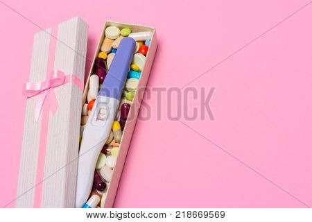 Treatment of infertility with pills help in conceiving a child. Tablets from pregnancy do not work contraception. Positive pregnancy test with two strips in a gift box with a pink ribbon