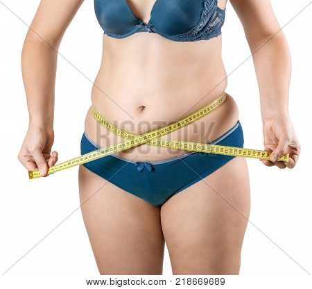 Fat girl with excess weight measures her belly and waist with a measuring tape. Woman in lingerie on white isolated background