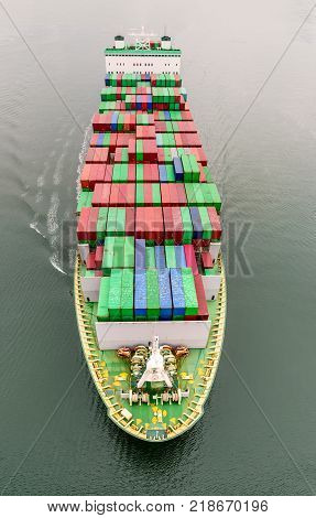 top view of a long modern ship - a container ship floating in the ocean along the waves