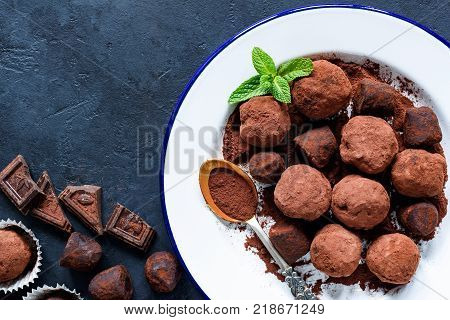 Homemade raw chocolate truffles decorated with mint on white plate and pieces of dark chocolate. Table top view, copy space for your text.