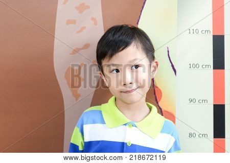 Little boy checking his height at school with measuring height scale on the wall by himself.Smiling cute asia boy measures his height. Boy growing concept