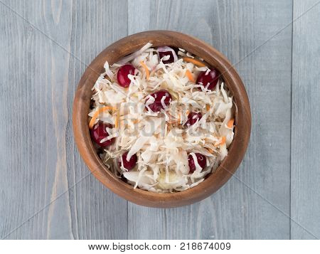 Traditional russian appetizer sauerkraut with cranberry and carrot in wooden bowl on gray rustic wooden table. Fermented cabbage. Russian cuisine and russian kitchen. Top view or flat-lay.
