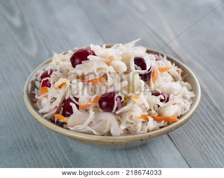Traditional russian appetizer sauerkraut with cranberry and carrot in craft plate on gray rustic wooden table. Fermented cabbage. Russian cuisine and russian kitchen.