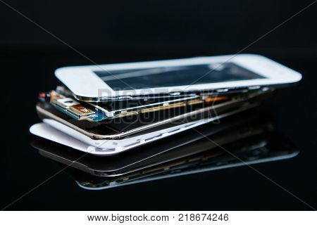 layered smartphone disassembly on black background. microelectronics workshop courses.