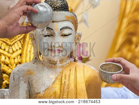 BATHING BUDDHA STATUE FOR BLESSING - A RELIGIOUS RITUAL. Buddhists believe that pouring water onto Buddha statue is a gesture of worship to the lord Buddha, and would bring them prosperity and happiness.