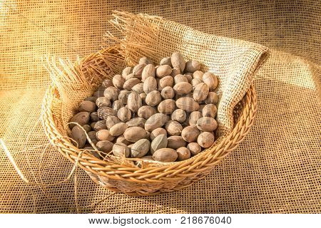 Pecans in basket wrapped with burlap textile with morning sunlight from window. Close up shot