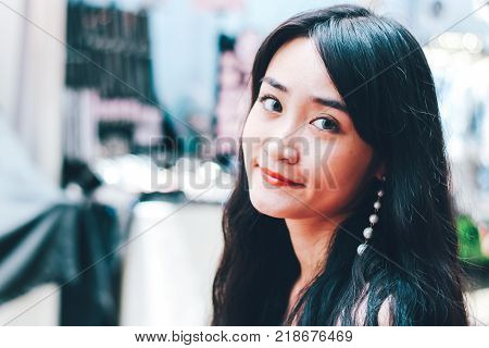 Close up of beautiful Asian woman with city blurred background.