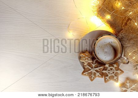 frothy cappuccino in transparent cup on a background of blurred lights garlands and figured cookies top view / festive coffee break