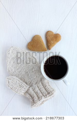 two gingerbread hearts warm mitten and mug with coffee on the table top view / atmosphere with warm feelings