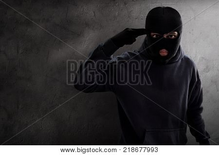 Masked thief threatening to killing the hostage