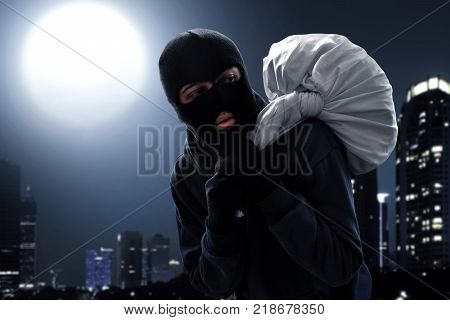 Masked thief escape carrying bag of money