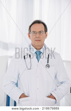 doctor standing with hands in pockets and looking at camera