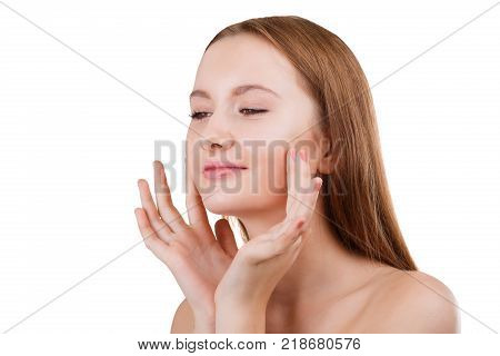 A sweet and attractive young brunette girl, without make-up and bare shoulders, does facial massage with fingertips. Isolated on white background.