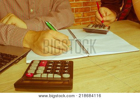 Young Business people Calculating Finance Bills In Office. Businesspersons working in office - Retro color
