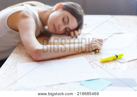 Young European brunette girl, asleep at work at the desk with documents. Indoors in the office.