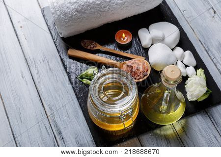 White bath towel, bee honey, aroma oil, burning small candles, buds of beautiful white flowers and various pebbles for spa and aroma procedures on a dark stone board. View from above.