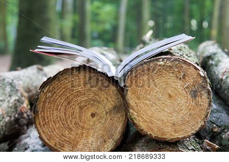 An open book lies on felled trees Save the trees - read e-books