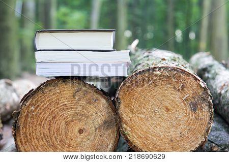 Books lying on felled trees Save the trees - read e-books