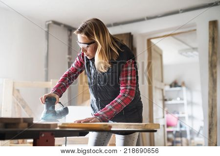 Young woman worker in workroom. Female carpenter using a sander.