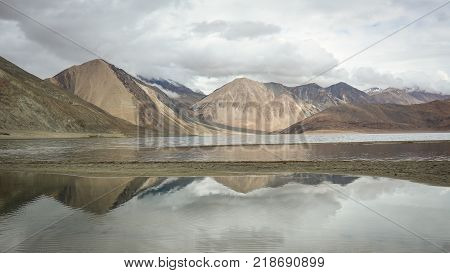 Reflection Pangong Lake with mountains in Ladakh North India.