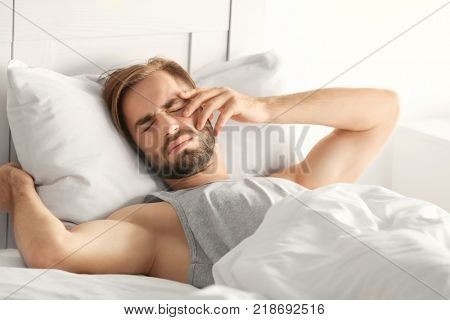 Morning of young man suffering from hangover at home poster