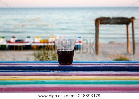 A plastic glassof wine stands on the colored bench the sea and the catamarans in the background