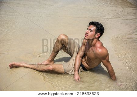 Handsome young man laying down on a beach in Phuket Island, Thailand, shirtless wearing boxer shorts, showing muscular fit body