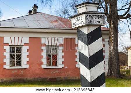 Retro stylized wooden milepost in Russian countryside. Text in Russian means distance to Pskov and St.Petersburg in versts