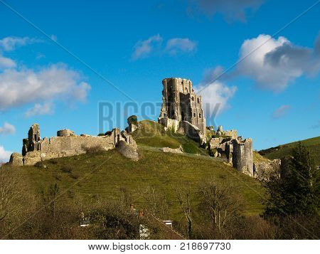 Corfe Castle in Dorset Corfe Castle, England - November 21, 2017: View of Corfe Castle in the Purbeck Hills of Dorset seen from the hills