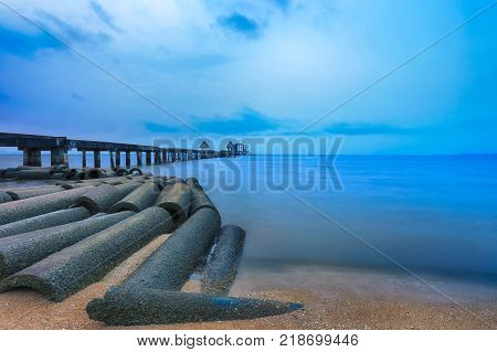 Old bridge in the sea on twilight time after sunset nature of outdoor tropical coast in Thailand of Popular attractions the name is Wat Jit-ta-pha-wan in Chonburi province.