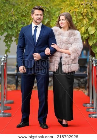 Beautiful young couple on red carpet, outdoors