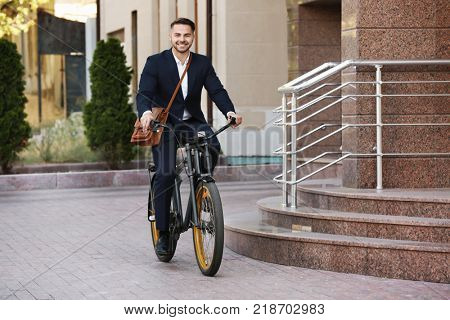 Young handsome businessman riding bicycle outdoors