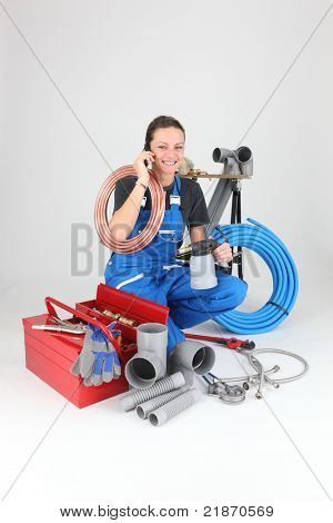Female labourer speaking on mobile telephone surrounded by equipment