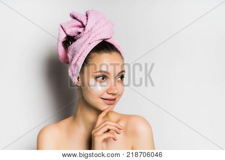 attractive young girl with a pink towel on her head and silicone patches under her eyes, looking away
