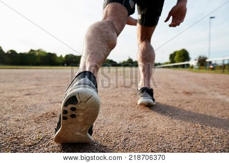 Low section of male runnerâ??s legs ready to run at a track