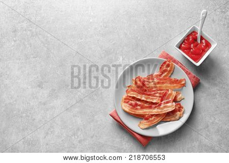 Plate with cooked bacon rashers and sauce on table