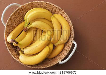 Basket with tasty ripe bananas on color background