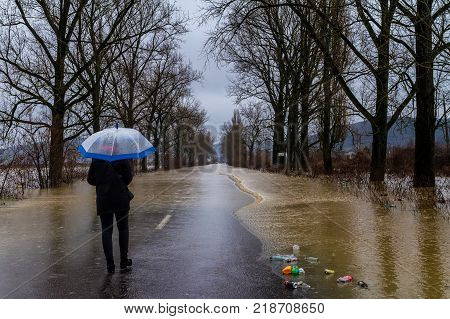 Syltse Ukraine - December 16 2017: Local girl with an umbrella walking on a flooded road during the winter floods near the village Syltse.