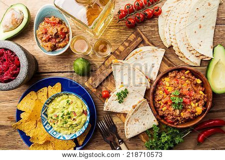 Mexican food mix: nachos, fajitas, tortilla, guacamole and salsa sauces and ingredients over wooden background. Top view