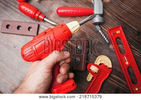 A Toy Drill In A Man's Hand And Other Tools On A Wooden Background