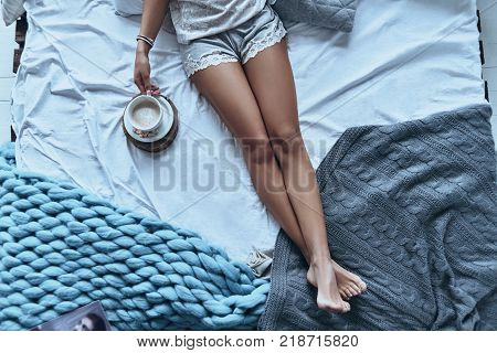 Coffee in bed. Close up top view of young woman having morning coffee while lying on the bed at home