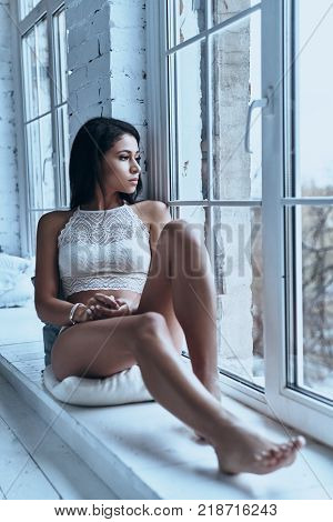 Quite contemplation. Attractive young woman looking away through the window while sitting on the window sill at home