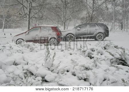 Snowstorm, snow-covered street and cars. Cars covered in snow during snowstorm cars covered snow winter falls snow. Snow-covered street and cars. Heavy snowstorm. Ukraine. KYIV.