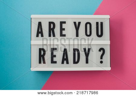 Are you ready - text on a display on blue and pink bright background.
