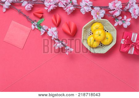 Table top view aerial of accessories and Chinese new year and Lunar new year festival background concept.Mix variety object for the season.Orange and accessories on red backdrop at home office desk.