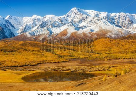 A Lake in a Valley under a Snow-Covered Mountain Range. Altai, Russia.