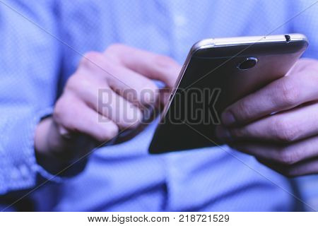 A young man in the bright shirt is in correspondence on the smartphone. Concept Manager, and businessman