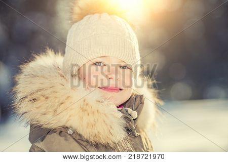 Portrait of little girl in sunny winter park